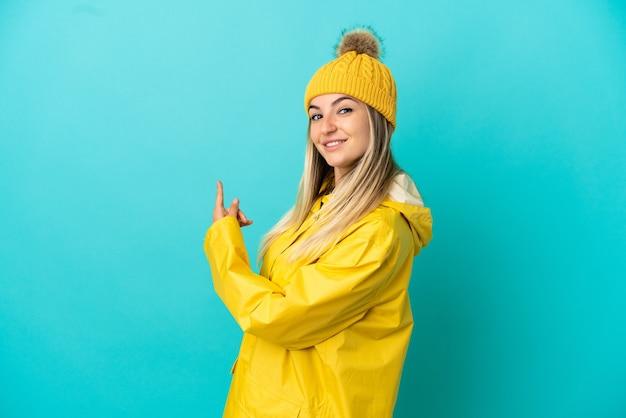 後ろ向きの孤立した青い背景の上に防雨コートを着ている若い女性