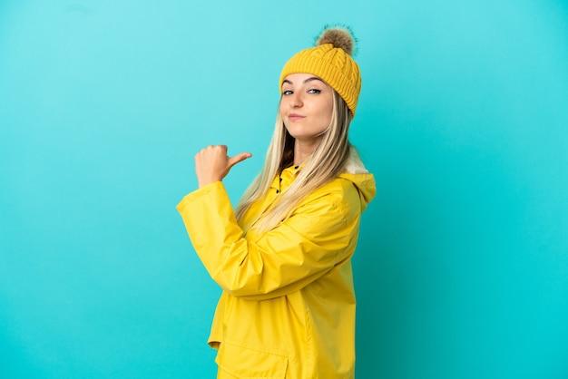 誇りと自己満足の孤立した青い背景の上に防雨コートを着ている若い女性