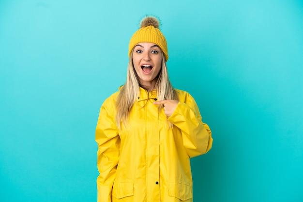 驚きの表情で孤立した青い背景の上に防雨コートを着ている若い女性