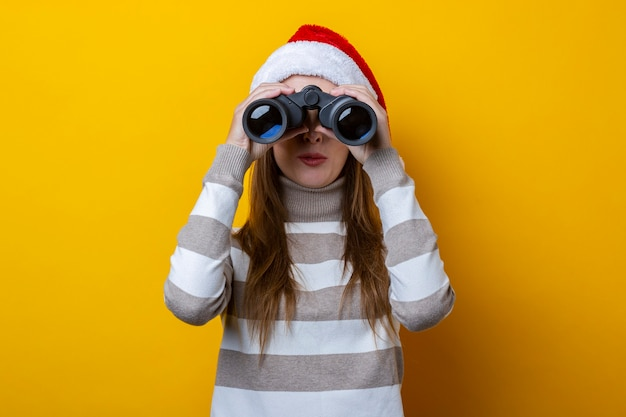 산타클로스 모자를 쓴 젊은 여성이 노란색 배경에 쌍안경을 통해 보입니다.