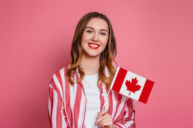 Молодая женщина в полосатой красной рубашке, улыбаясь и держа маленький флаг канады и глядя на камеру, изолированных на розовом пространстве, празднование дня канады