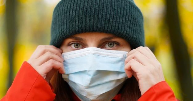 Молодая женщина в теплой шапке и защитной медицинской маске для защиты от вирусов, микробов