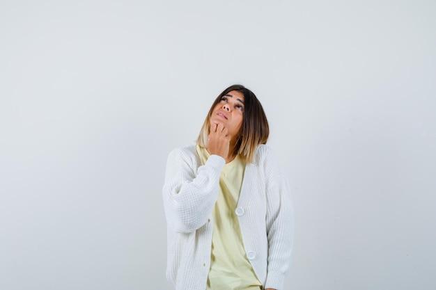 考えている白いカーディガンを身に着けている若い女性