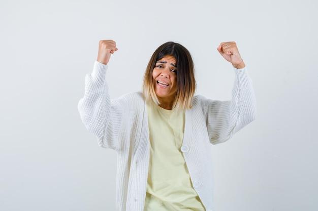 優勝した白いカーディガンを着た若い女性