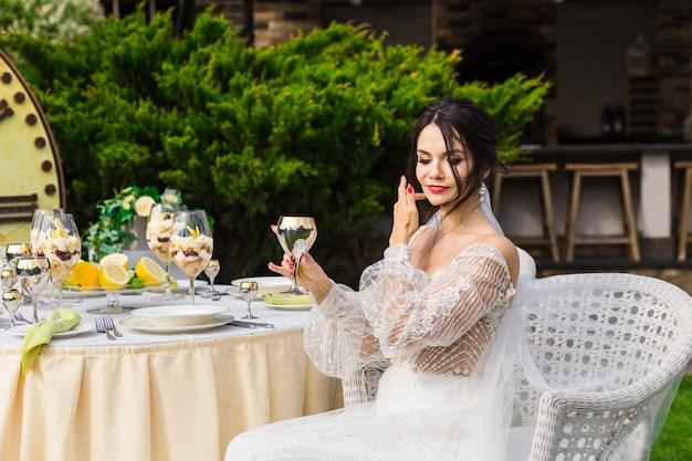 白いドレスを着て、太陽の光の中でシャンパングラスを持っている若い女性。野外パーティーのコンセプト。