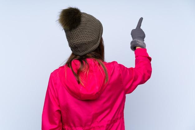 孤立した背景に冬の服を着た若い女性