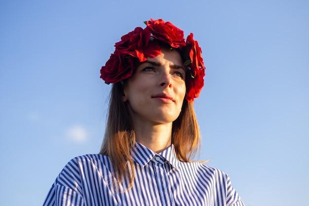 青い空を背景に夕日を楽しむ赤い花の花輪を身に着けている若い女性。