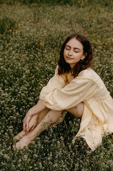 野花と野原に座っている黄色のドレスを着て若い女性