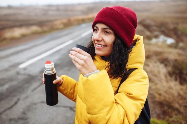 黄色いジャケット、バックパック、赤い帽子をかぶった若い女性が、魔法瓶からお茶を飲んでいる空の冬の道の脇に立っています。