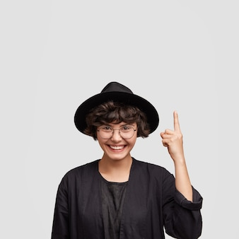 Young woman wearing all black clothes and round eyeglasses