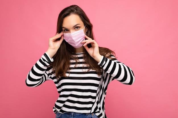 분홍색 배경 위에 고립 된 코로나 covid-19 및 sars cov 2 감염으로부터 다른 사람을 방지하기 위해 안티 바이러스 보호 마스크를 착용 한 젊은 여성.