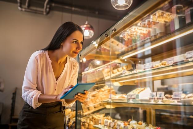 パン屋でエプロンを着ている若い女性