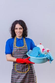 Молодая женщина в фартуке и резиновых перчатках, держащая таз с чистящими средствами, смотрит в камеру с улыбкой на лице, стоя на белом фоне