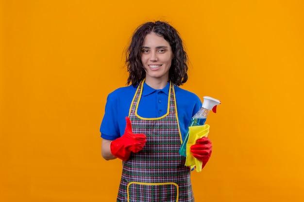 Молодая женщина в фартуке и резиновых перчатках держит чистящий спрей и коврик, глядя в камеру с большой улыбкой на лице, показывая пальцы вверх, стоя на оранжевом фоне