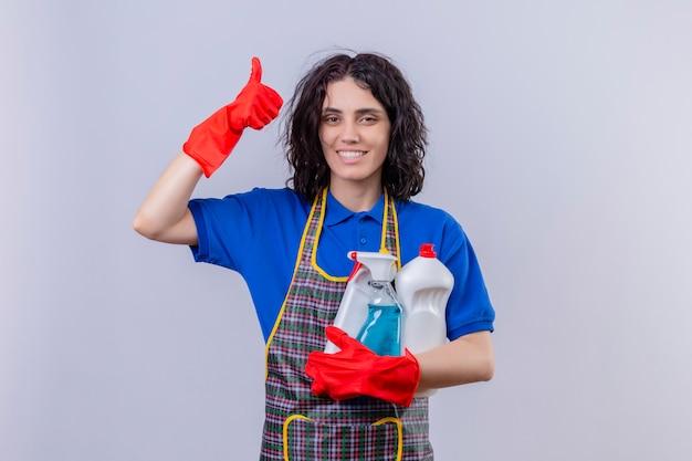 白い壁の上に親指を現して顔に笑顔でクリーニング用品を保持しているエプロンとゴム手袋を着用した若い女性