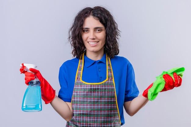 敷物を押しながら白い壁の上の顔に笑顔でスプレーを洗浄エプロンとゴム手袋を着用して若い女性