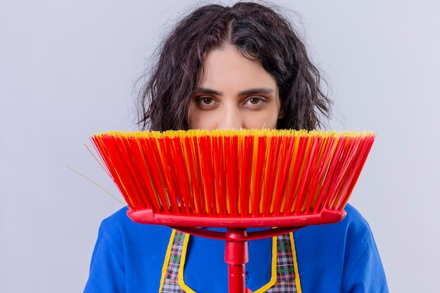 Young woman wearing apron hiding behind a mop looking at camera slyly over white background
