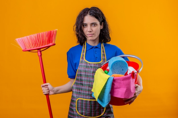 Giovane donna che indossa il grembiule tenendo la benna con strumenti di pulizia e mop guardando la fotocamera con seria espressione fiduciosa in piedi su sfondo arancione