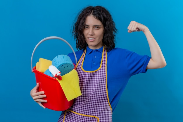 Young woman wearing apron holding bucket with cleaning tools raising fist showing biceps smiling confident, ready to clean over isolated blue wall