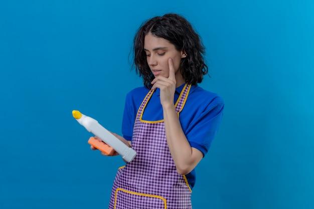 Rifornimenti di pulizia d'uso della tenuta del grembiule della giovane donna che lo esaminano espressione pensierosa di pensiero sopra la parete blu