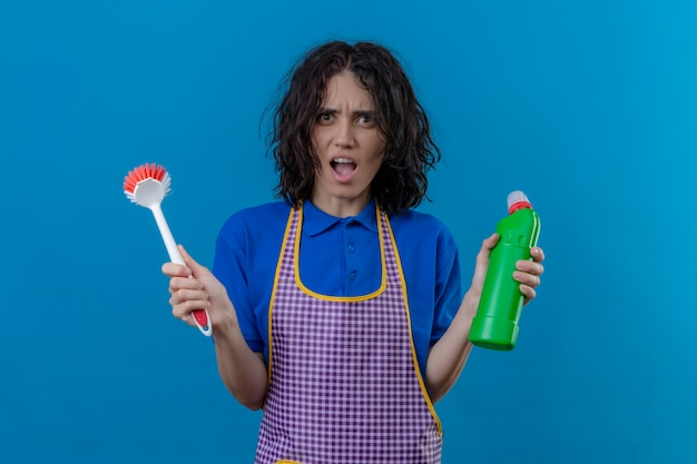 Молодая женщина в фартуке, держащая щетку и бутылку чистящих средств, потрясена широко открытым ртом, стоящим на синем фоне