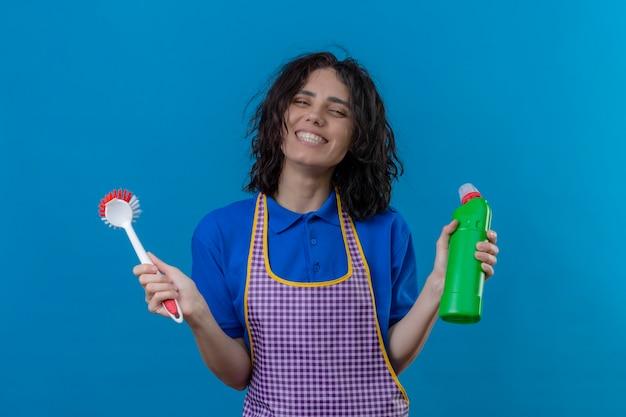 Giovane donna che indossa un grembiule tenendo la spazzola e una bottiglia di prodotti per la pulizia sorridendo allegramente guardando gioiosa in piedi su sfondo blu