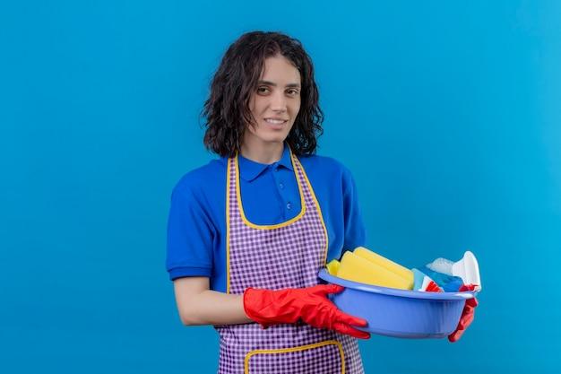 Giovane donna che indossa un grembiule e guanti di gomma tenendo il bacino con strumenti di pulizia guardando la fotocamera con il sorriso sul viso in piedi su sfondo blu