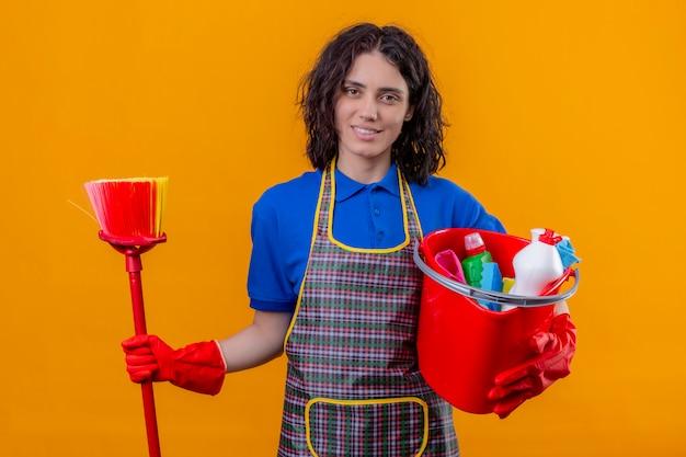 Grembiule d'uso della giovane donna e guanti di gomma che tengono secchio con gli strumenti di pulizia e sorridere mop sorridenti amichevoli sopra la parete arancio