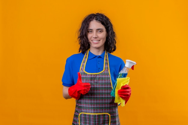 Young woman wearing apron and rubber gloves holding cleaning spray and rug looking at camera with big smile on face showing thumbs up standing over orange background