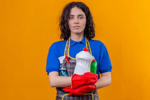Young woman wearing apron and rubber gloves holding cleaning supplies with serious confident expression over isolated orange wall