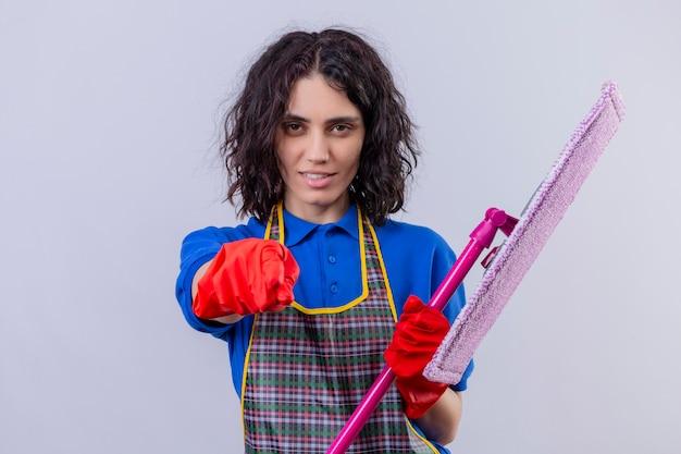 Grembiule d'uso della giovane donna e guanti di gomma che tengono zazzera e che indicano con il dito la macchina fotografica che sembra sicura sopra la parete bianca