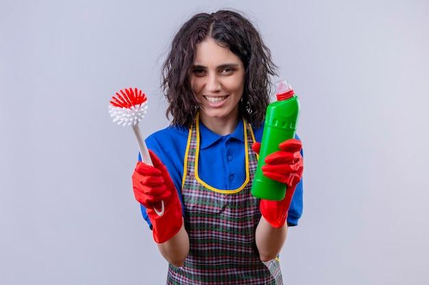 Giovane donna che indossa un grembiule e guanti di gomma tenendo la spazzola per strofinare e una bottiglia di prodotti per la pulizia sorridente allegramente cercando gioiosa in piedi su sfondo bianco