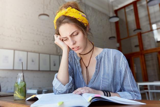 バンダナを着て、カフェで勉強している若い女性