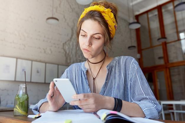Молодая женщина в бандане и учится в кафе