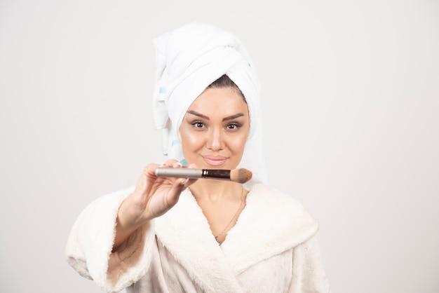목욕 가운과 수건을 착용하는 젊은 여자는 메이크업 술을 사용합니다.