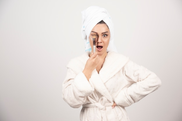 バスローブとタオルを身に着けている若い女性は、メイクアップにタッセルを使用しています