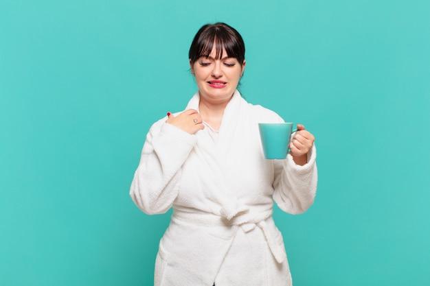 목욕 가운을 입은 젊은 여성은 스트레스, 불안, 피곤, 좌절감을 느끼고 셔츠 목을 당기고 문제에 대해 좌절감을 느끼고 있습니다.