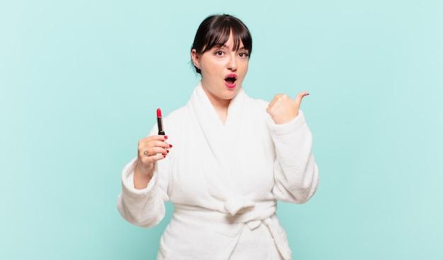 バスローブを着た若い女性は、信じられないことに驚いて、横の物を指差して、すごい、信じられない、と言った。