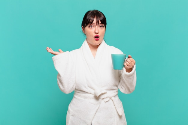 Young woman wearing bathrobe looking surprised and shocked, with jaw dropped holding an object with an open hand on the side