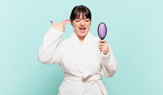 불행하고 스트레스를 받는 목욕 가운을 입은 젊은 여성, 머리를 가리키는 손으로 총 기호를 만드는 자살 제스처