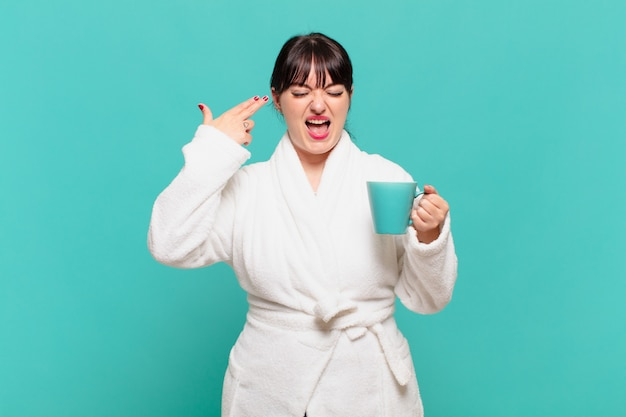 Young woman wearing bathrobe looking unhappy and stressed, suicide gesture making gun sign with hand, pointing to head