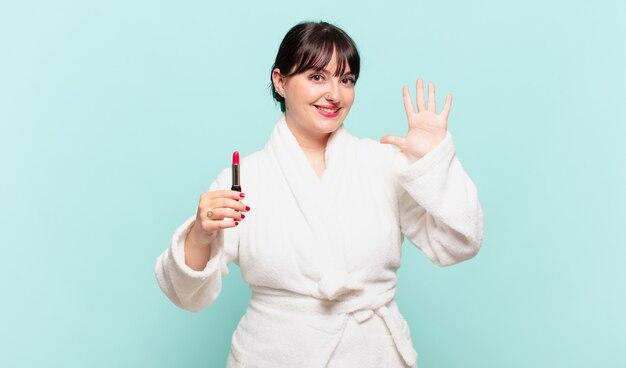Молодая женщина в халате улыбается и выглядит дружелюбно, показывает номер пять или пятое с рукой вперед и считает
