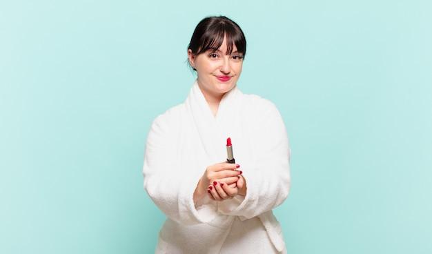 バスローブを着た若い女性は、フレンドリーで自信に満ちた、前向きな表情で幸せそうに笑って、オブジェクトやコンセプトを提供し、示しています