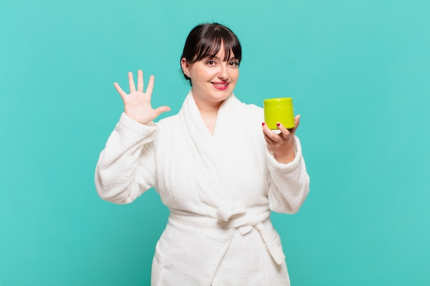 Young woman wearing bathrobe smiling and looking friendly, showing number five or fifth with hand forward, counting down