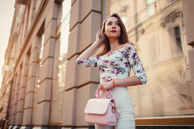 Young woman wearing beautiful outfit and accessories outdoors. girl holding handbag. fashion model walking in city