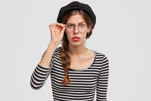 Giovane donna che indossa berretto e camicia a righe