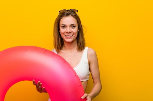 Молодая женщина в бикини, держащая надувной пончик, счастливая, улыбающаяся и веселая.