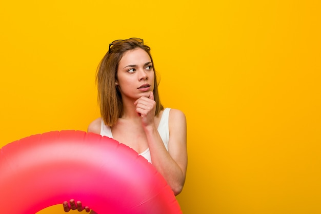 Young woman wearing bikini holding an inflatable donut looking sideways with doubtful and skeptical expression.