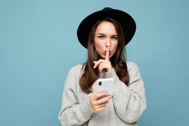 검은 모자와 회색 스웨터를 입은 젊은 여성이 스마트폰을 들고 카메라를 쳐다보며 배경에 격리된 쉿 제스처를 보여줍니다