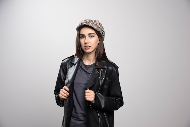 Young woman wearing black leather jacket and cap.
